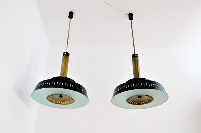 Large original pair of 1950s Stilnovo model #1157 made of painted metal, brass and textured (knurled) glass. Produced from Stilnovo Italy approximately during 1956-1957. The chandeliers are made of black painted metal and patinated brass with