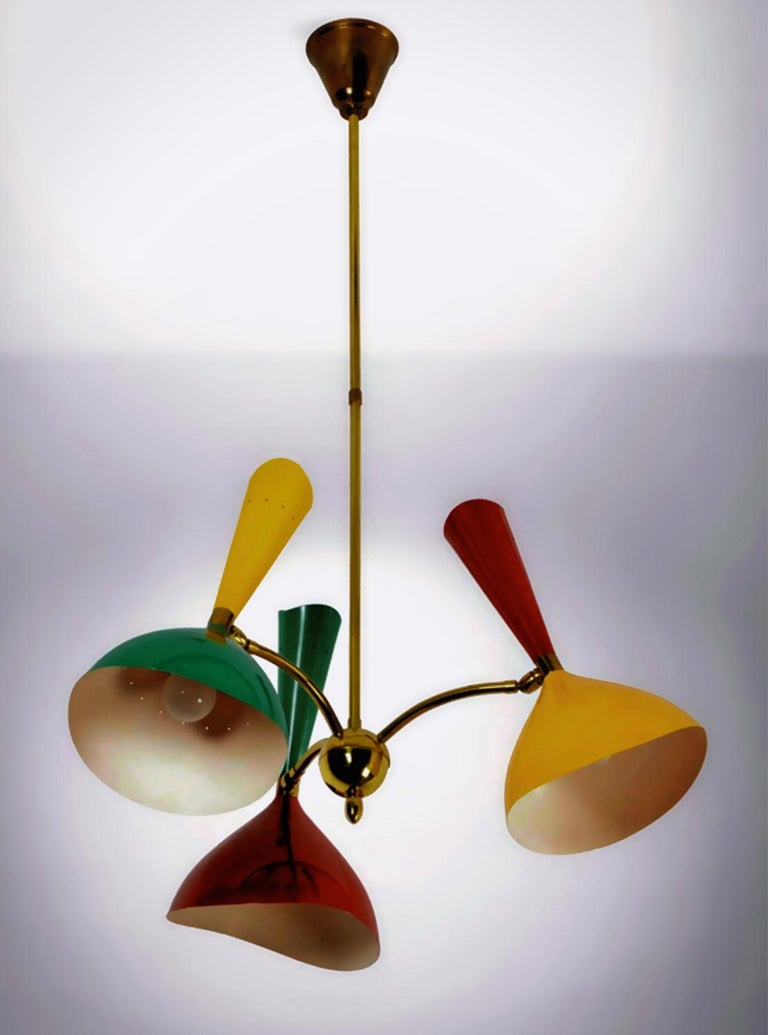 Superb Italian chandelier by Stilnovo of the 1950s. It's equipped with three brass arms, each one with a metal lacquered diabolò shade in a double colour, all provided with hinge joints permitting their single angular adjustment in all