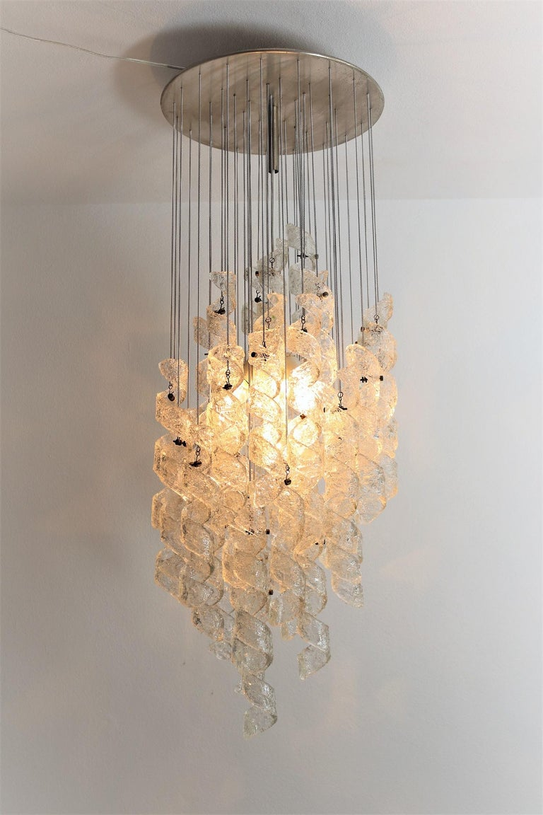 Gorgeous and rare chandelier with 43 pieces of curly transparent Murano made ice-glasses which are hanging from a chromed ceiling plate down on chromed chains of different length. The chandelier is made during the 1970s in Italy from Milan company