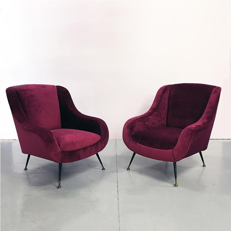 Italian midcentury cherry red velvet and brass armchairs, 1950s. Couple of Italian velvet armchairs dating to the fifties with completely restored structure and new padding inside and cherry red velvet outside. Metal legs with brass tips and curved