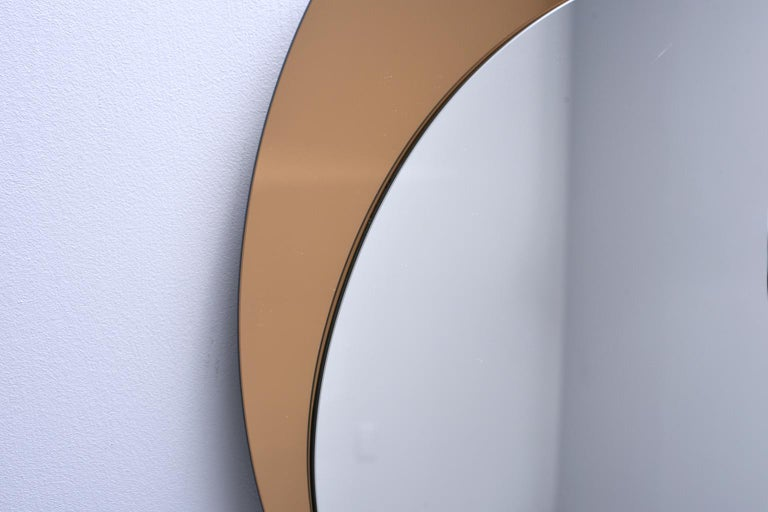 Italian mirror features a bronze colored circular mirror with off-center silver mirror overlay. Unknown maker. Very good vintage condition, circa 1970s.