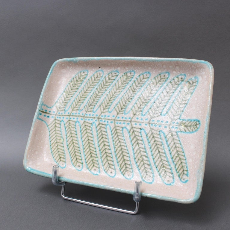 Italian decorative ceramic tray by Guido Gambone (circa 1950s). Adorned on the tray surface you will find a stylised fern motif in matt blue and green on an oatmeal-coloured background. The lip is highlighted in a mix of the same colors. The