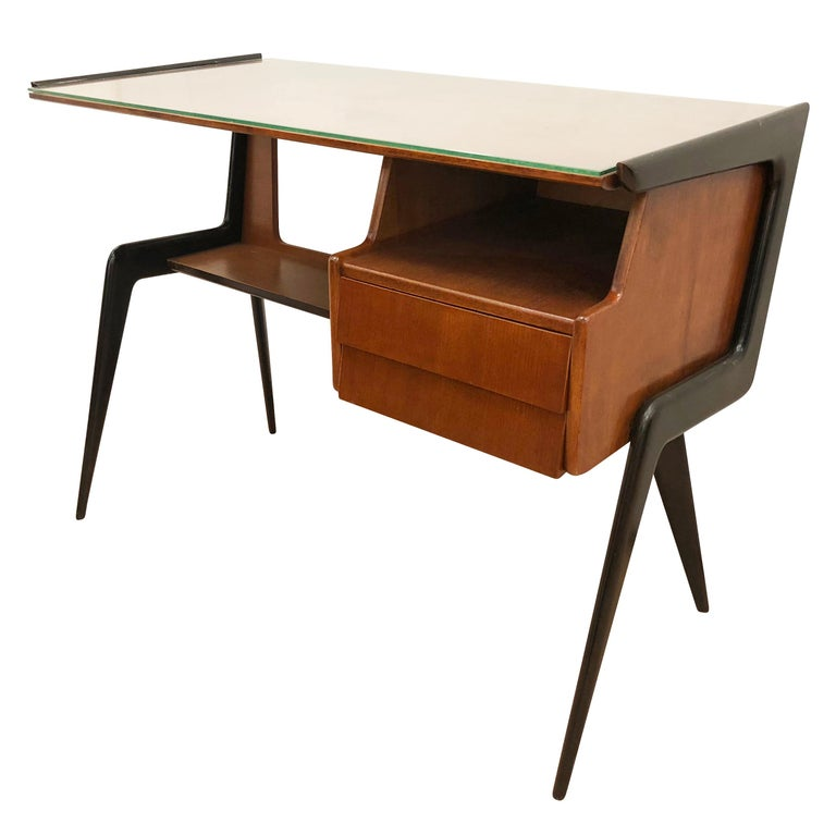 Beautiful Italian midcentury desk in the manner of Silvio Cavatorta. Walnut body with ebonized legs. Has a clear glass top and two drawers.
