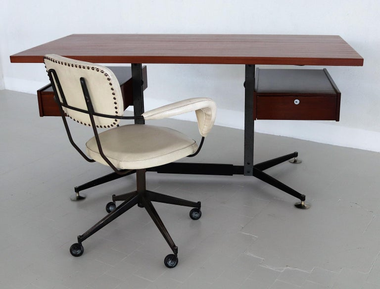 Large and stylish executive Italian desk from 1960s production with veneer cover in mahogany, inspired by the style of Gio Ponti. The architect's desk has a solid and heavy steel base with vintage stains on the metal. The round feet are made of