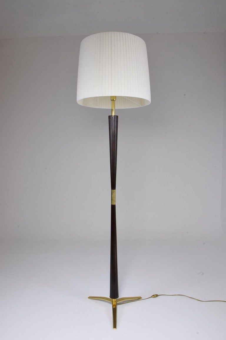 Majestic 20th century vintage floor lamp by notable lighting manufacturing company Stilnovo circa 1950s-1960s designed in solid carved mahogany, brass details, and base. Professionally rewired and in fully restored condition with a new white soft