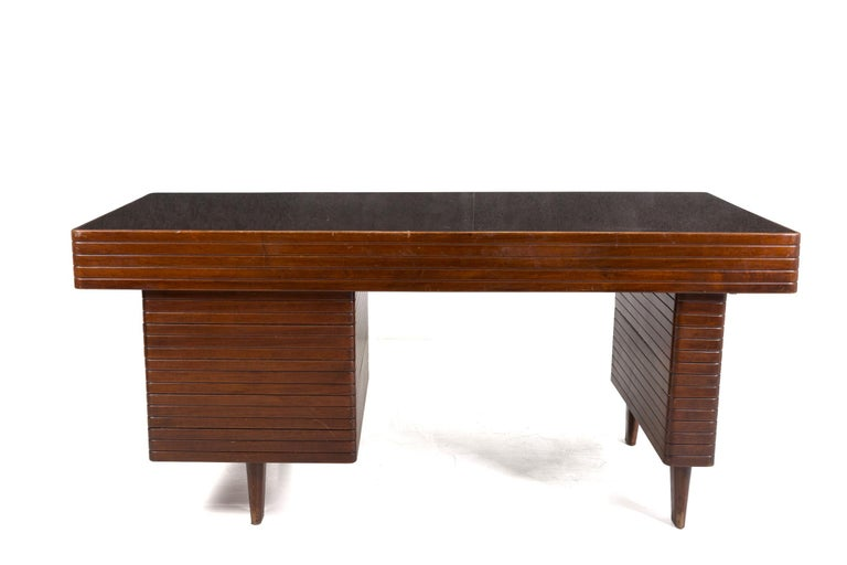 Magnificent desk attributed to Gio Ponti of the 1950s. The desk is made of walnut wood grissinatura. It has been attributed to the great Italian designer because of its realization and its typical lines. The desk has a dark colored glass top that
