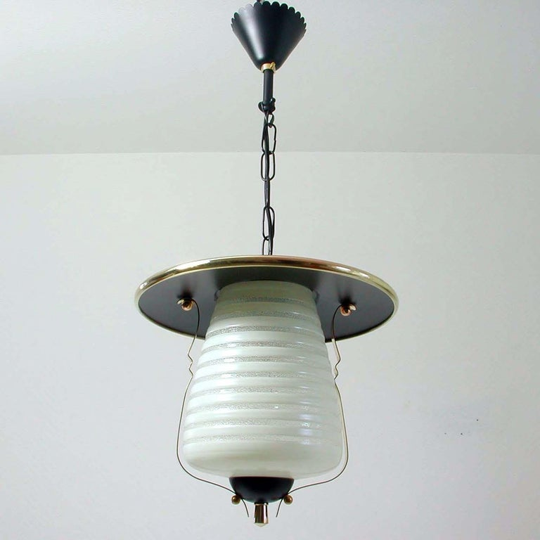 This vintage lantern ceiling light was made in Italy in the 1950s. It is made of black lacquered metal, frosted glass and has got brass details.