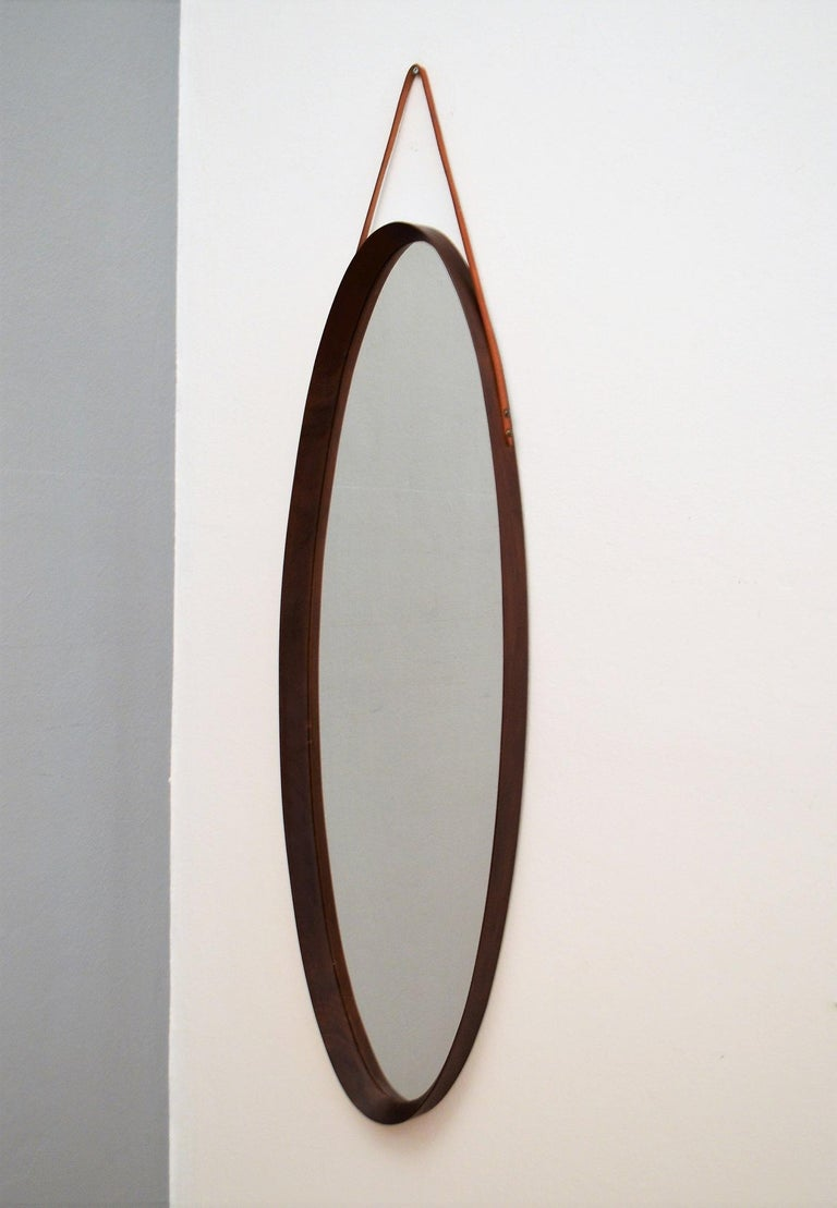 Gorgeous midcentury long wall mirror with beautiful frame of mahogany wood and leather strap for wall hanging. Made in Italy in the 1950s. Please have a closer look to the quality of the wooden frame and its joints, made from artisan hand. There
