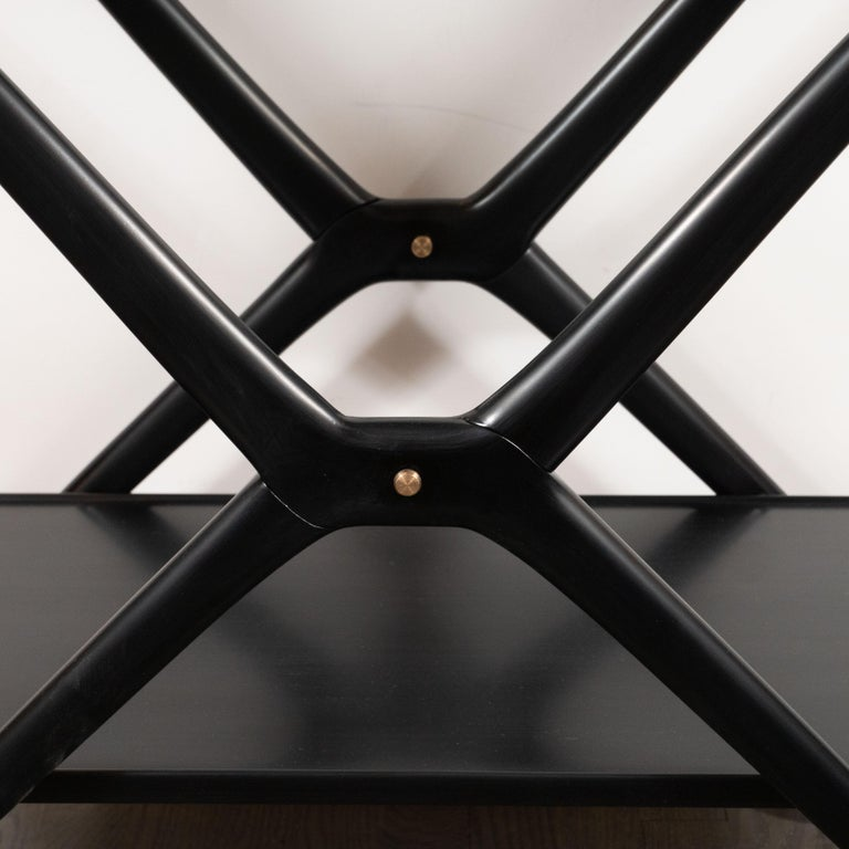 This striking bar cart, designed by the great Mid-Century Modern designer Ico Parisi, was realized in Italy, circa 1950. Composed of two tiers- a glass top with a detachable tray beneath - and an ebonized walnut body, this piece offers a wealth of