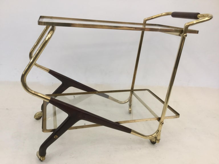 A 1950s Italian bar cart in brass with wood legs.