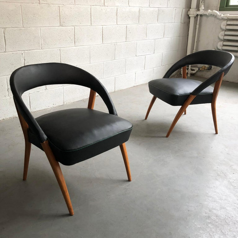 Pair of Italian, Mid-Century Modern, lounge chairs feature wonderfully shaped maple frames with rounded backs upholstered in black vinyl with green piping.