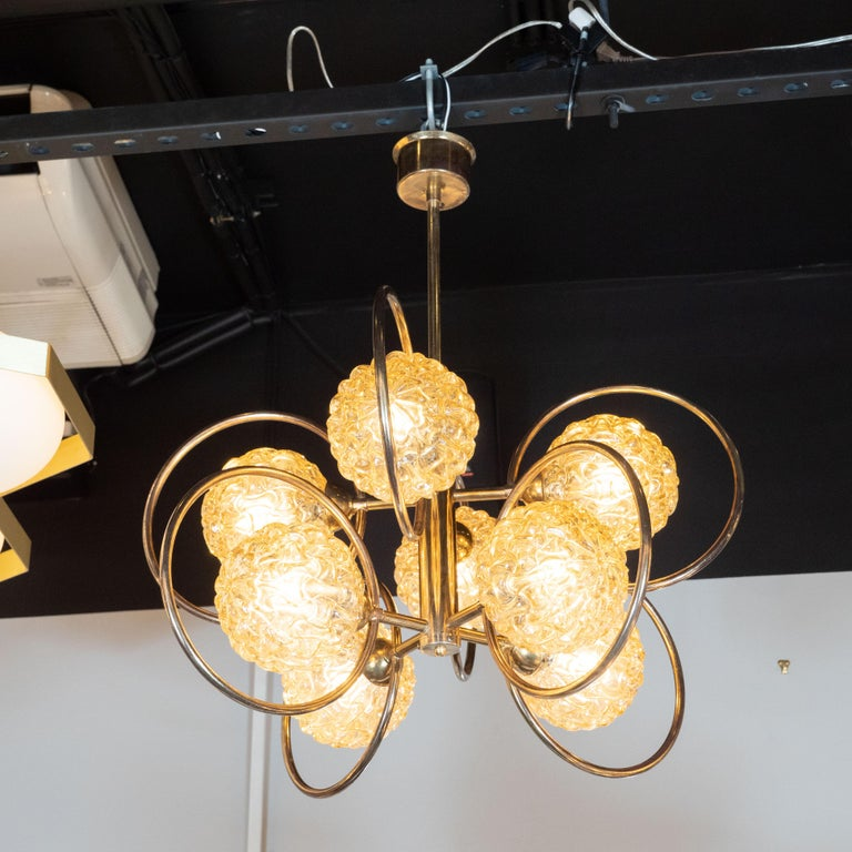 This Mid-Century Modern patinated brass chandelier was designed and produced in Italy, circa 1970. The fixture is suspended from a brass rod that connects to a central brass cylinder. Eight rods connect perpendicularly to this central cylinder, each
