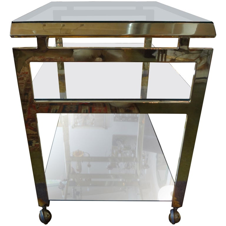 Italian Mid-Century Modern seamless brass bar cart, serving cart, drinks cart or cocktail trolley. This Italian service cart has an Asian modern feel with two new glass and mirrored shelves. Featured Italian brass bar cart in the style of Milo