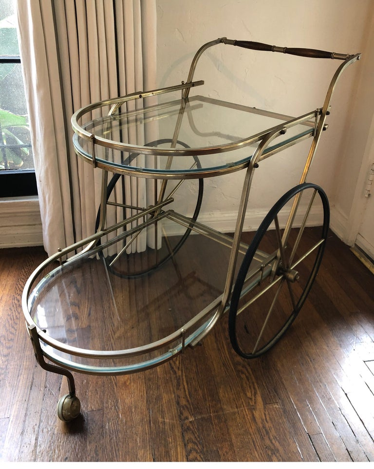 Large Italian two-tiered bar car. Brass finish with clear glass shelves. Two large wheels on each side that glide smoothly and one front wheel/caster. Walnut handles. Overall good condition with some signs of age on brass consistent with age.