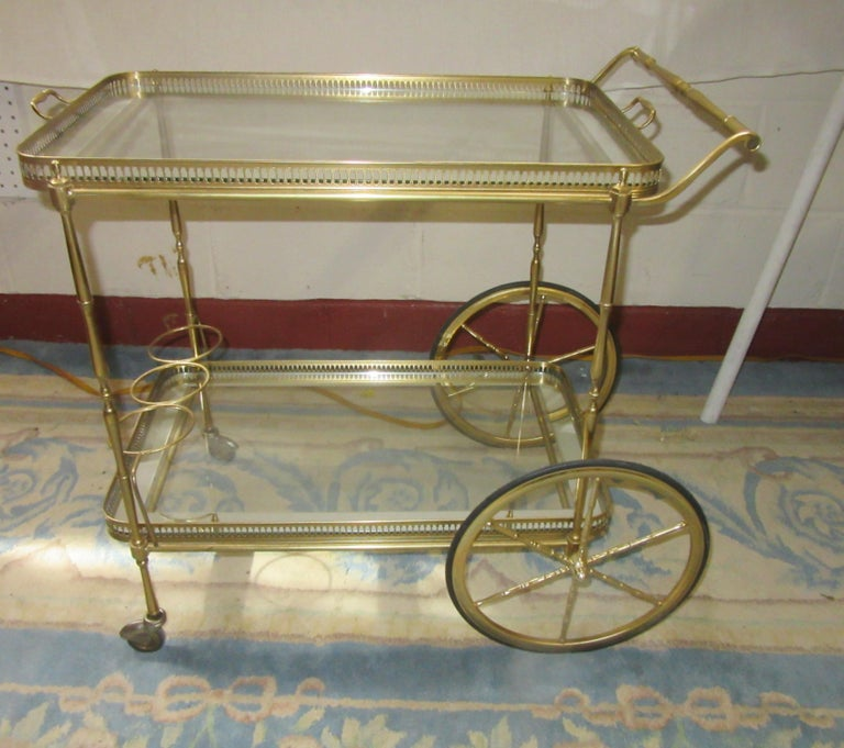 Mid-Century Modern Italian brass bar cart with two shelves. The top shelf has a removable tray with a glass shelf and a silver border. The bottom shelf has a glass shelf with a silver border and a holding place to store 3 bottles.