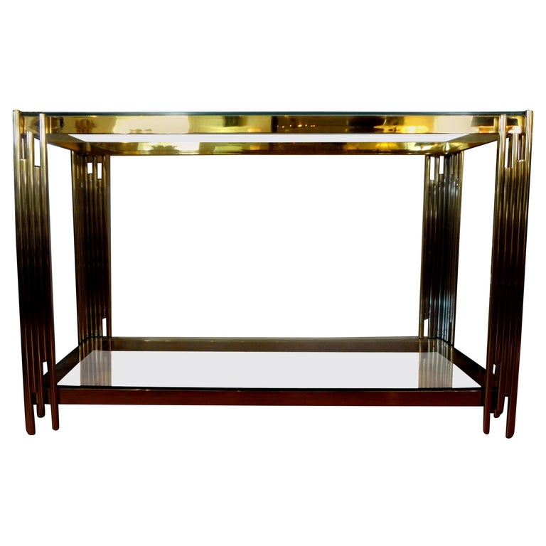 Stunning Italian modern brass two-tiered console table with glass tops. This fabulous Italian midcentury Romeo Rega style free standing Italian made geometric modernist console table is in very good vintage condition and can be used as a sofa table