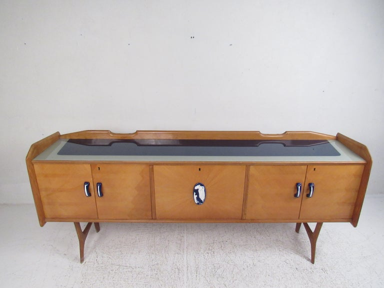 This stunning vintage modern sideboard features cobalt handles on the cabinet doors. An unusual Ico Parisi style design that has a two-tone glass top. The raised edges along the top add to the mid-century appeal. This sleek case piece offers plenty