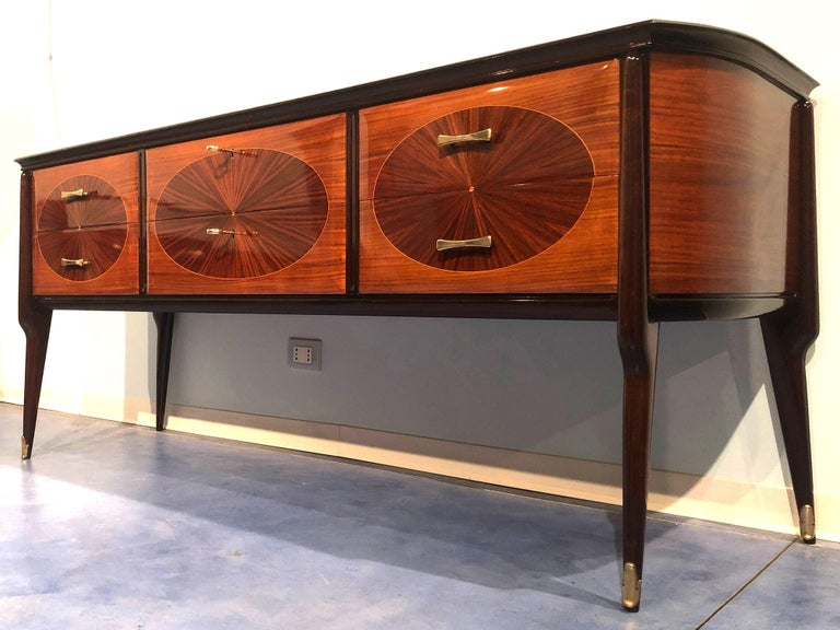 Elegant and modern but at the same time warm and cozy dresser, commode, or console by Vittorio Dassi. Finely veneered with oval motif drawers, on top black glass, legs ending in severe bronze sabots.  In very good condition ready to use.