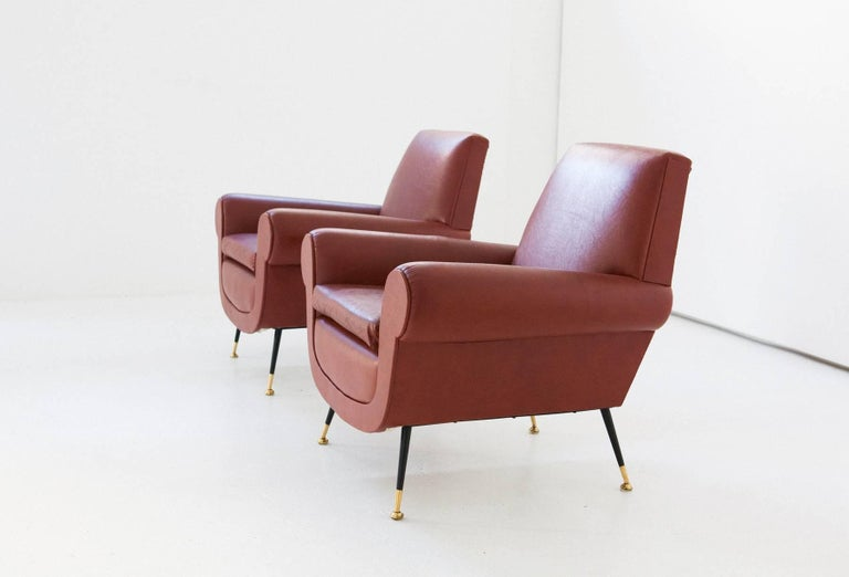 Set of two armchairs in faux brown or orange leather with iron legs and brass feets Italian design by Gigi Radice for Minotti 1950s.  The upholstery and upholstery are original and are in good condition You can request the replacement of the