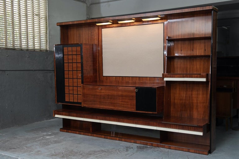 Italian Mid-Century Modern rosewood large living room bookcase with storage, white lacquered details on the drawers and a fabric upholstered panel to put the TV or a painting, is has also three lamps over the upholstered panel.