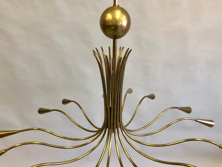 Elegant Italian Mid-Century Modern brass pendant / chandelier by Stilnovo. The chandelier is composed entirely of brass with natural antique patina and is circular / round in form with 16 arms. The piece has a sensuous gently undulating motion to