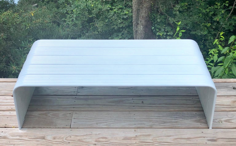 Italian Mid-Century Modern white enameled aluminum bench attributed to Superstudio.  The bench is in reverse U-shaped form and composed of a series of grooved pieces of aluminum. It is light and designed to be easily transported as they will