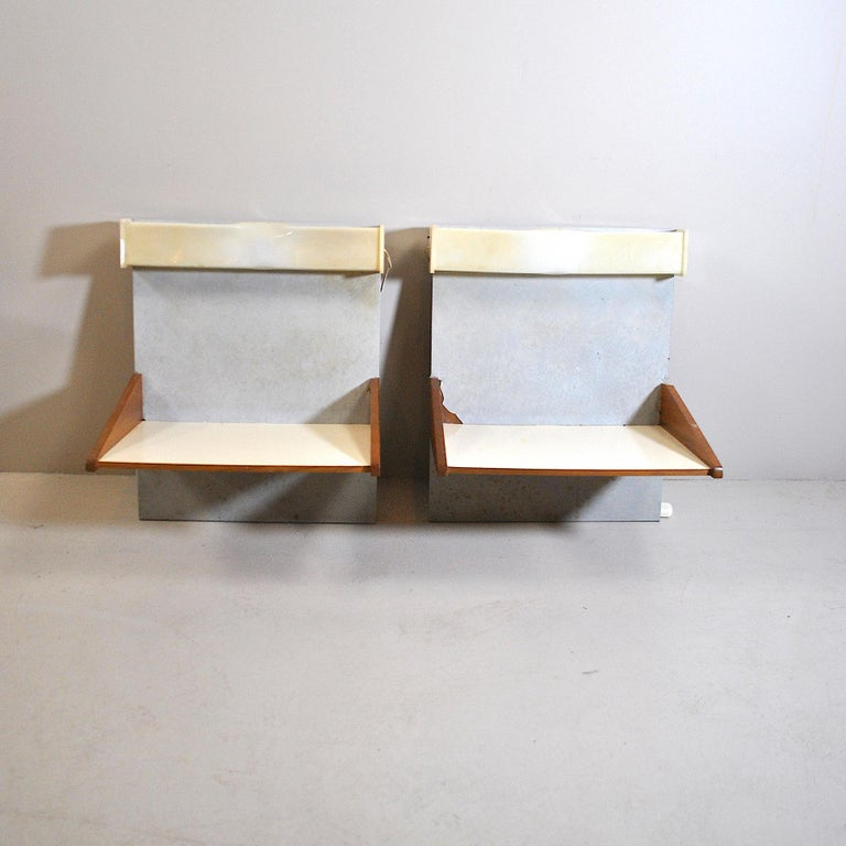 Pair of wall-mounted wooden bedside tables with lights incorporated in a plexiglass structure.