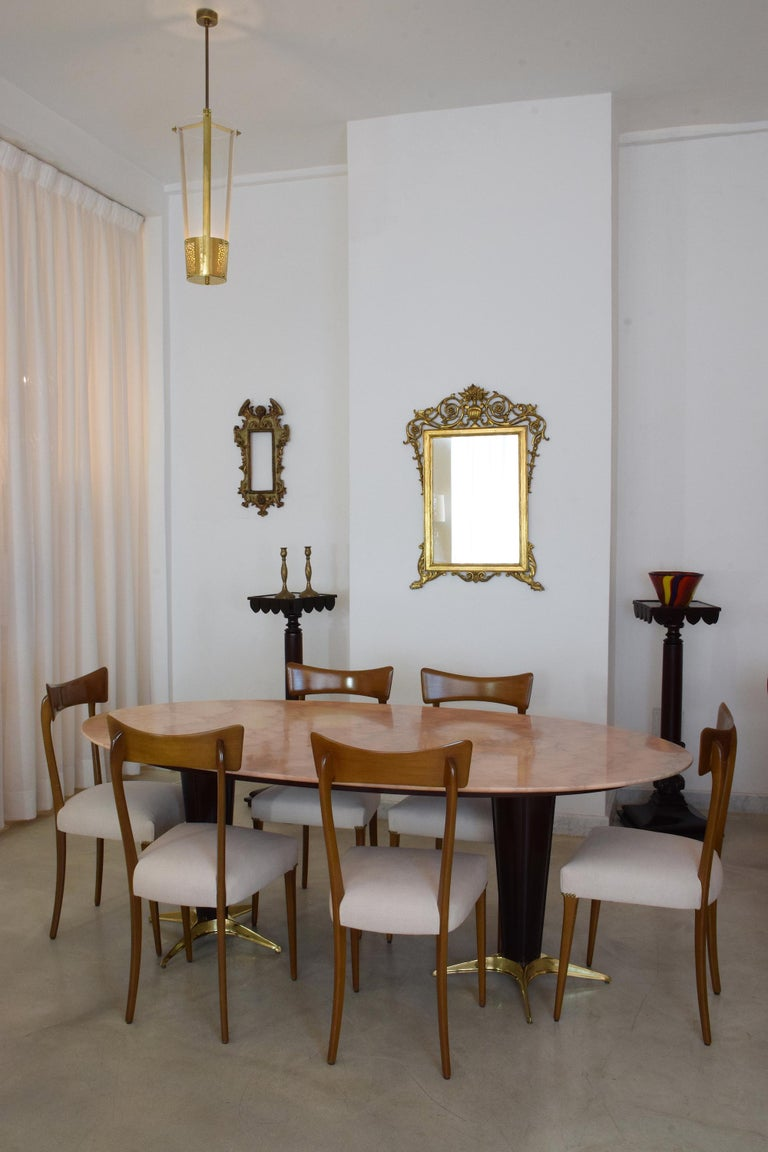 A 20th century 8 seater vintage oval dining table composed of a Rosa Portuges pink marble tabletop and a mahogany veneer structure with sculptural star shaped endings. In restored condition with new finishing, polishing and careful cleaning.  Italy,