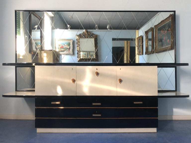 This Italian midcentury sideboard has splendid contrast movement of the lines, the lower part is lacquered in black, the design takes influence from the geometric rationalism form, the higher part has interesting demilune shape.