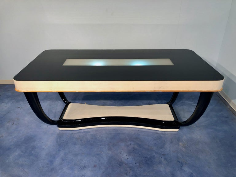 Luxurious and stylish Italian midcentury parchment dining table with an illuminated black glass top. The table legs are really elegant in black lacquered mahogany wood. The tableside is in parchment, you can notice a maple line on the final part.