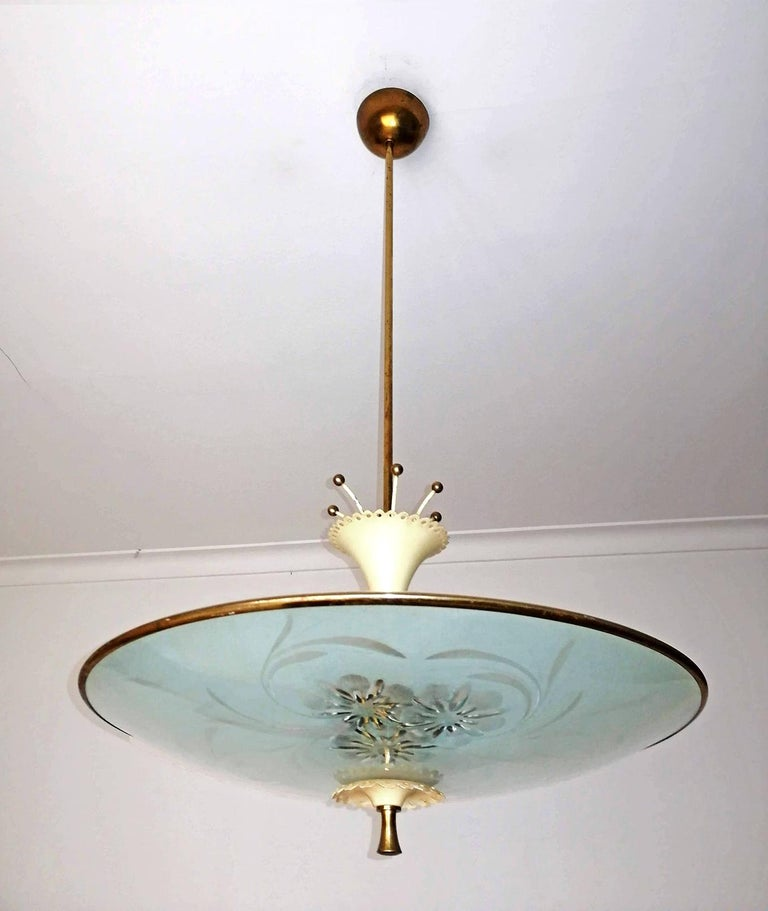 A large Mid-Century Modern vintage flying saucer chandelier. Made of solid brass and etched convex glass with two frosted glass domes. Takes 6 standard sockets, up to 60 watts each for 360 watts total. Age patina. Measures: Diameter 21.6 in/ 55