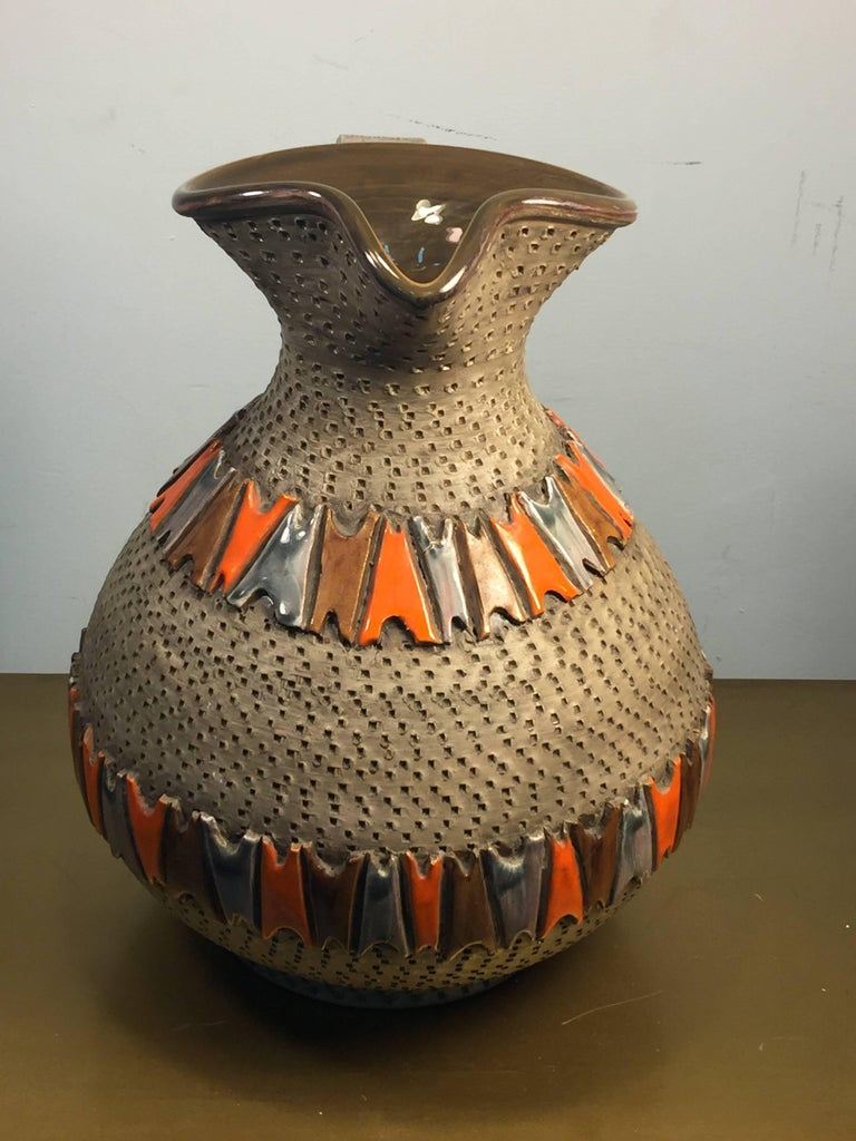 Italian pottery pitcher formed in the Brutalist manner with brown rough textured background and geometric glazed designs in deep brown, orange and gray. Created in Italy, circa 1950s-1960s, the base measures at 6 1/2