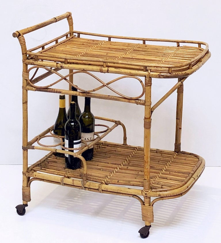 A fine Italian handcrafted mid-century rattan and bamboo bar cart or drinks trolley. Featuring a two-tiered body with decorative accents - the top tier with a gallery and handle over a bottom tier with fittings for six bottles.  Great for a patio or