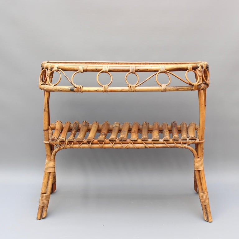 Italian rattan console table (circa 1960s). A very stylish piece with character and charm. There are two horizontal surfaces for storage or display, the top made of 1960s style laminate. The smart-looking cane legs and frame are fastened together