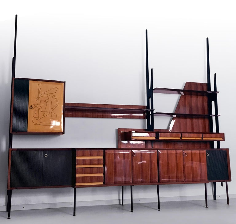 Fantastic Italian wall-mounted bookcase designed by Vittorio Dassi in the 1950s. It's very rare and represents one of the Mid-Century Modern masterpiece of the Italian design. The structure is in veneered rosewood, supported by uprights with the
