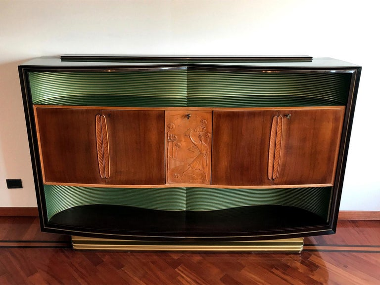 Stunning walnut Sideboard designed by Vittorio Dassi in the 1950s.  It's finished with two long shaped colored green glass that give it a particularly brightness, one placed on the top plane and the other one inside the hollow, internally crafted of