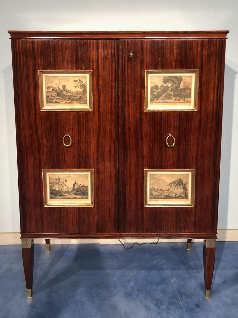 Italian mid-century cabinet bar or sideboard designed by Paolo Buffa in the 1950s. On the front doors, you find four giltwood panels, inserted with 18th-century engravings of classic scenes. The interior has drawers and mirrored shelves with stars
