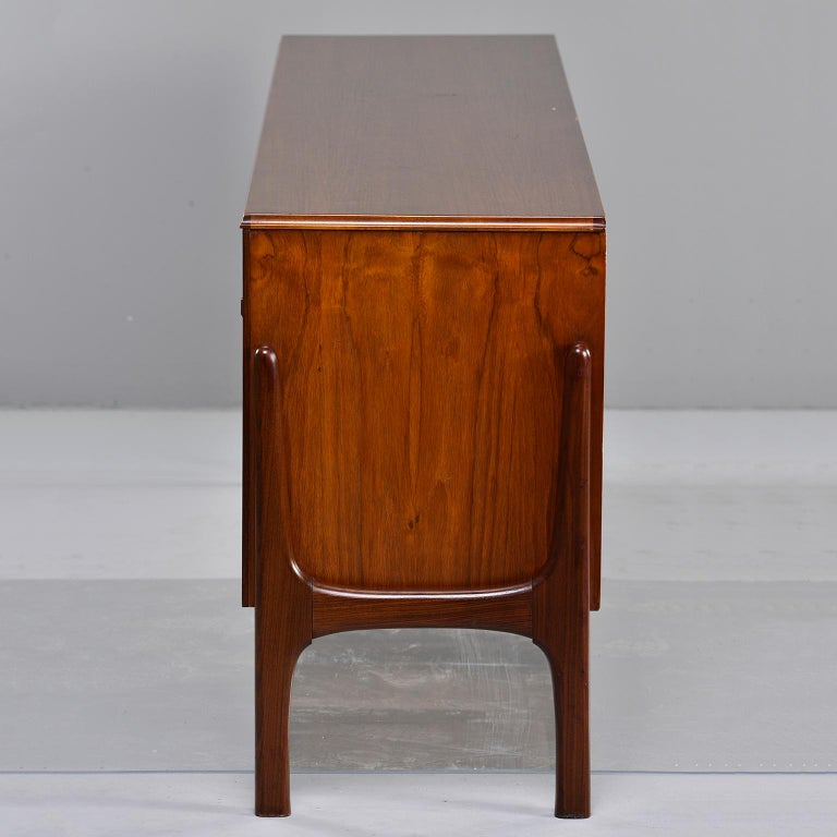 Italian credenza or sideboard made from wood of contrasting shades, circa 1960s. Long and streamlined body features storage cabinets with single internal shelves and sliding doors. There are also pull out shelves at bottom. Unknown maker. Very good