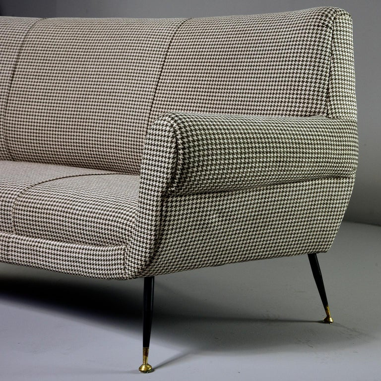 Sofa / settee designed by Gigi Radice for Italian maker Minotti, circa late 1950s. This iconic piece features curvy, midcentury Italian lines, narrow metal legs with black enamel finish and brass feet and new upholstery. Fabric is a short napped