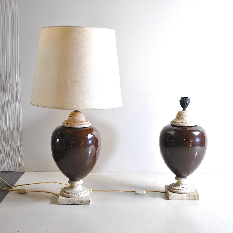 Pair of 1960s table lamps in brown glazed ceramic with travertine marble bases.  The lamps are sold without the lampshade in the picture, but it can be requested in the form, sizes and colors at will with an extra price.  n.b. the measures in
