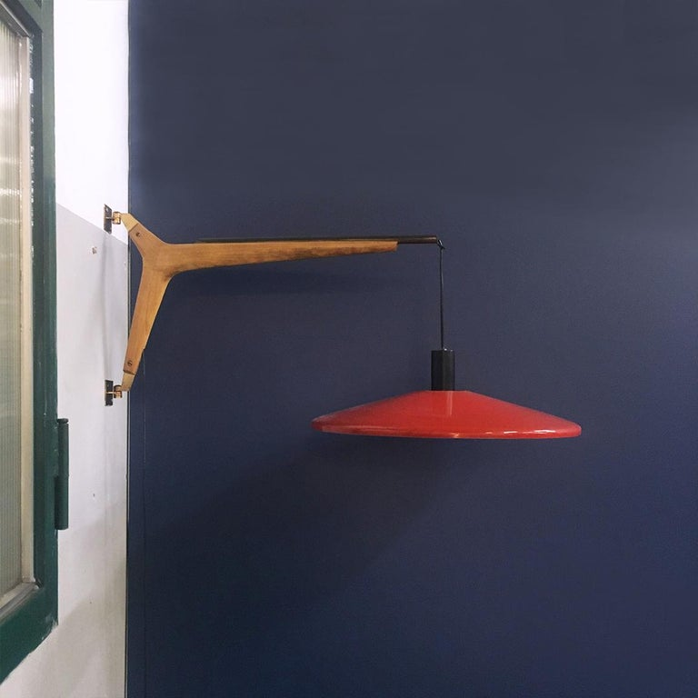 Italian midcentury telescopic wall lamp Stilnovo in solid wood and metal, 1950s. Telescopic wall lamp with solid wood structure, brass counterweight with up-and-down system, lampshade in red metal on the outside and white on the inside. Produced