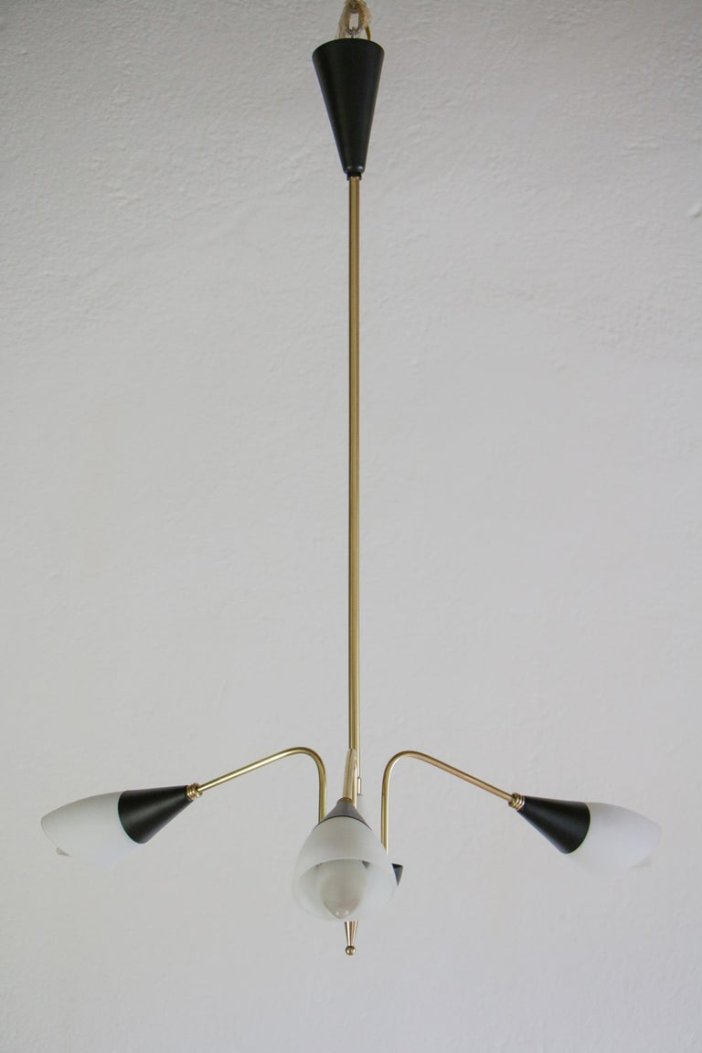 Refined Italian Mid-Century Modern chandelier pendant lamp attributed to Stilnovo fashion house from the 1960s. Composed of three lights E14 format, structure in polished brass, satin glass, black-painted aluminum. A specialized craftworker made