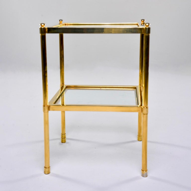 Italian side table has a brass frame with lower shelf and tabletop of clear glass, circa 1970s. Unknown maker. Very good vintage condition with scattered surface wear to glass and brass.