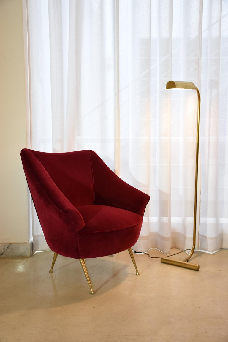 An Italian 20th century vintage brass-legged, curved armchair fully restored with one of the highest quality French upholstery makers, Lelièvre Paris in red velvet.  The sophisticated brass legs have been carefully polished.  A two-seater sofa of