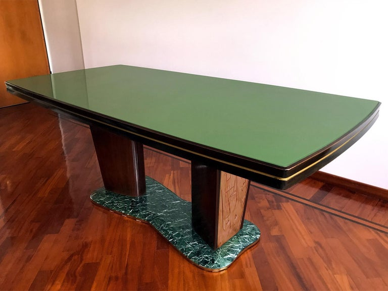 For your consideration this elegant dining table in Art Deco style, designed by Vittorio Dassi in the 1950s. The top-table has a glass back-treated with green colored paper and is supported by two big legs fixed on a basement made of precious