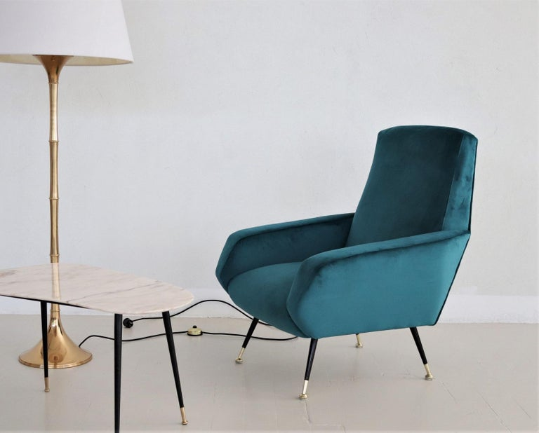 Beautiful and elegant Italian vintage armchair, original from the 1950s. The armchair have been restored completely internally with high quality material and reupholstered with petrol - blue colored soft velvet fabric. Legs are made of solid black