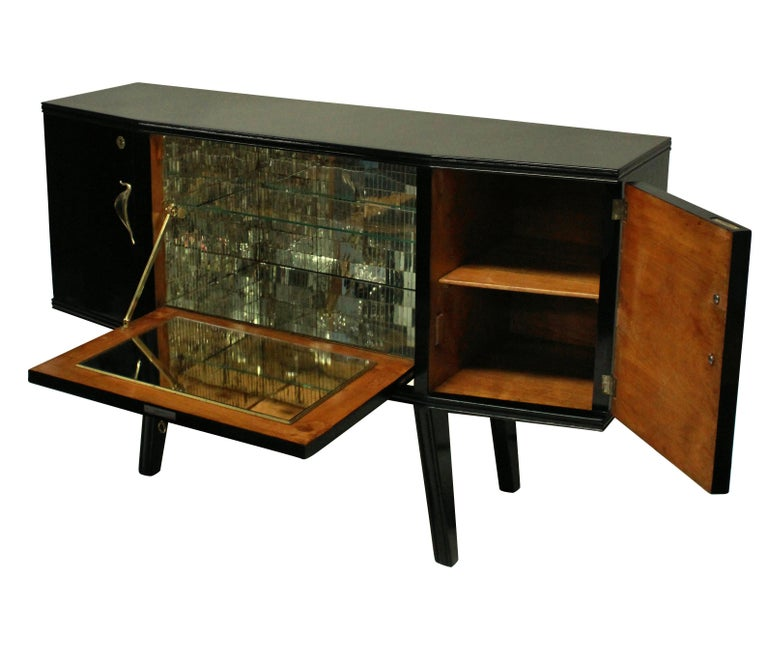 A stylish Italian bar credenza of interesting angular design in black lacquer with sapele wood interior, with brass hardware and a faux malachite central panel and mirrored interior.