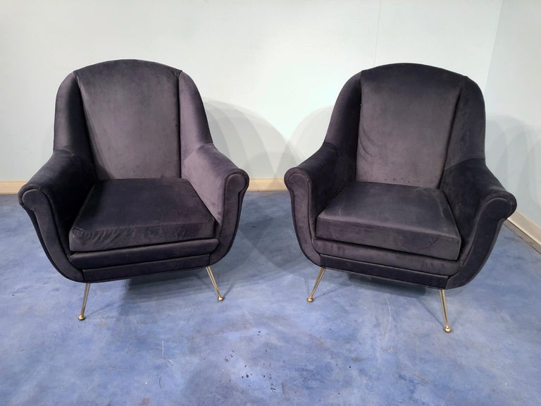A pair of very stylish and extremely comfortable Italian midcentury midnight blue velvet armchairs or club chairs in Gio Ponti style, original from the 1950s with polished brass legs. The seats are upholstered in blue stain-resistant velvet.