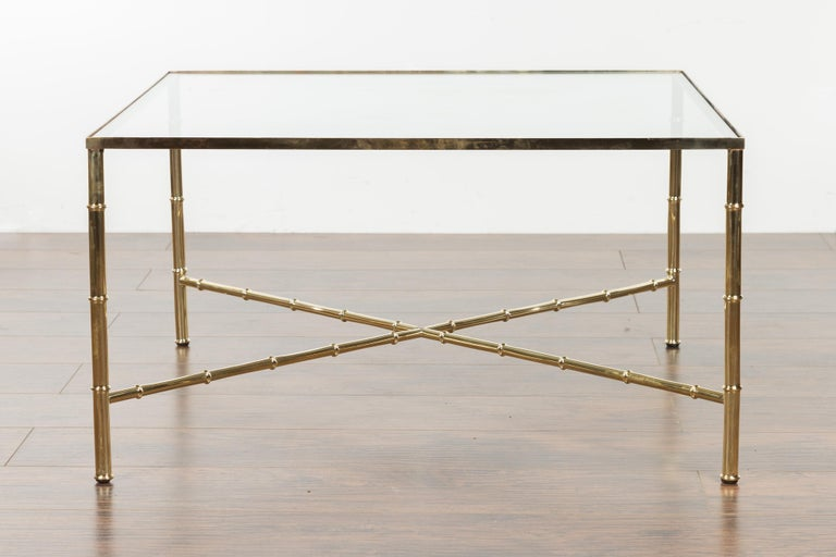 An Italian vintage brass coffee table from the mid-20th century, with glass top. Created in Italy during the midcentury period, this coffee table features a square glass top supported by four straight brass legs connected to one another through an