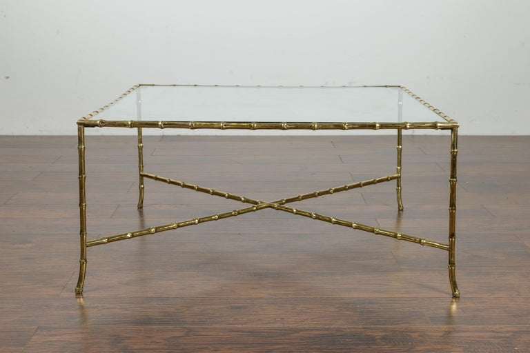 An Italian vintage brass coffee table from the mid-20th century, with glass top and faux bamboo base. Created in Italy during the midcentury period, this brass coffee table features a rectangular glass top sitting above an eye-catching faux-bamboo